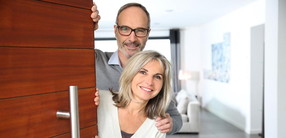 Älteres Paar steht an der Haustür, Holzhaustüre mit Metallgriff
