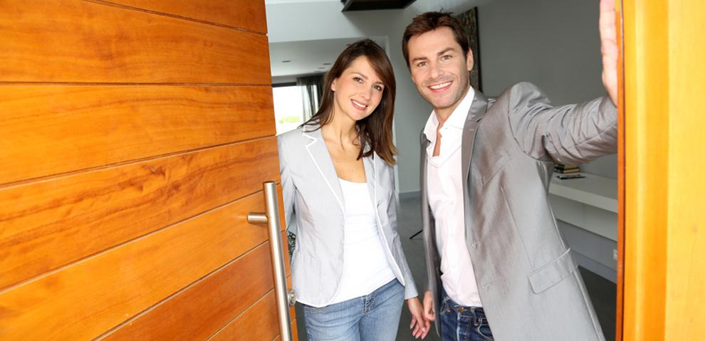 Paar steht an der Tür, Holzhaustür mit Metallgriff